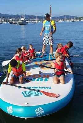 7 jeunes en cours de paddle collectif en Méditerranée