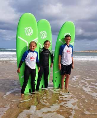 Pose photo devant leurs surfs pour ces 3 jeunes