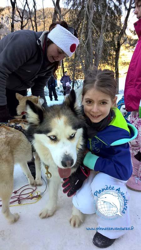La joie d'une petite fille en colonie de vacances Or blanc et chien de traîneau