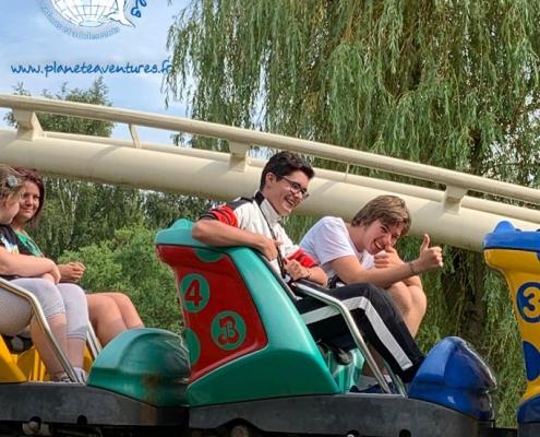 Des adolescents en colonie de vacances sont à bord des wagons du Grand-huit d'un parc d'attraction.