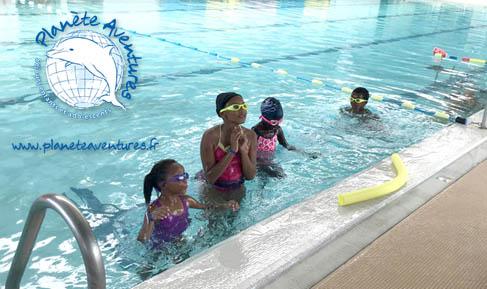 Des gamins dans le grand bassin, écoutent le maitre nageur.